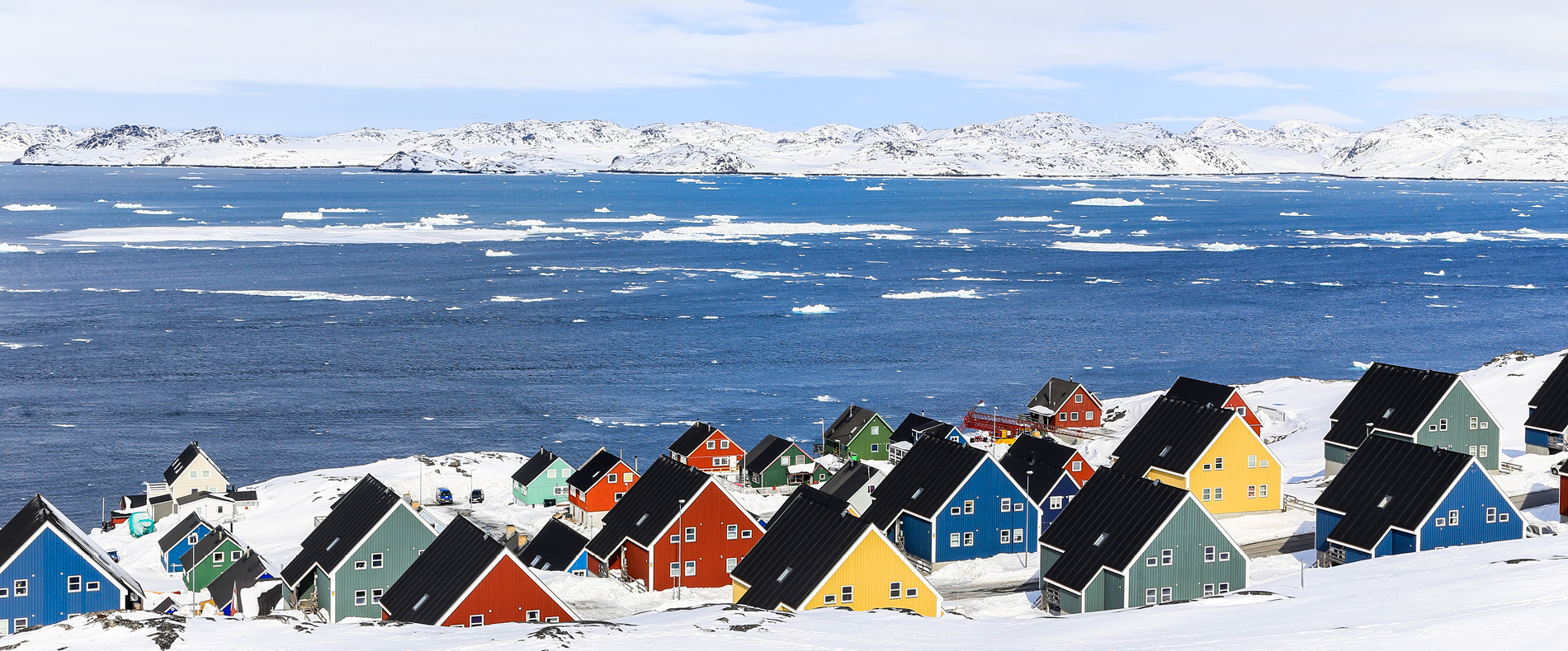 colourful houses surrounded by snow next to a body of water seen from a luxury Arctic cruise