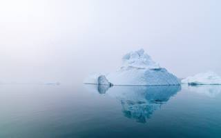 An iceberg shrouded in mist in a body of water