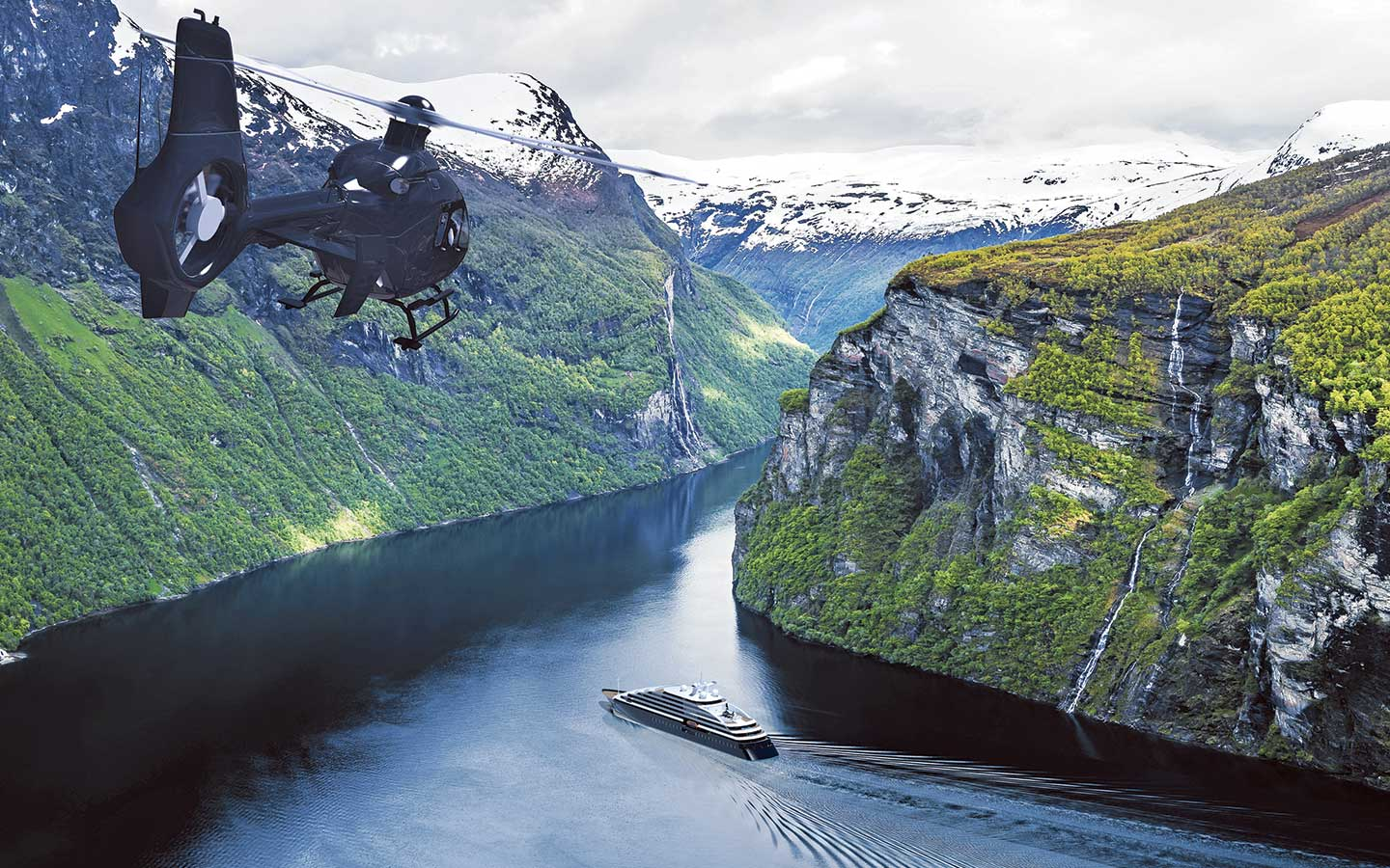 Scenic Eclipse expedition cruise sailing surrounded by snow covered mountains accompanied by a helicopter flying behind