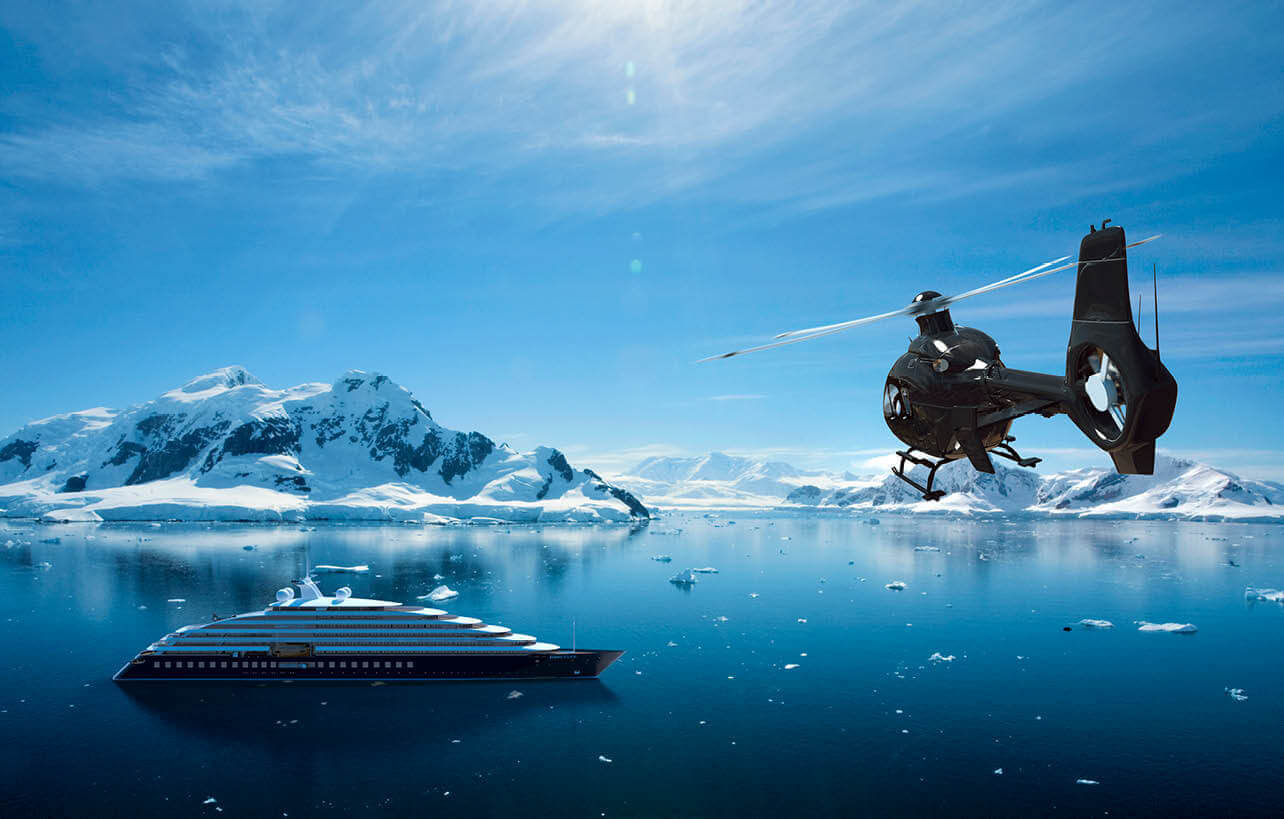 helicopter flying over Scenic Eclipse as it sails through the Antarctic with mountains in the distance