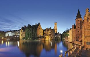 a castle with water in front of Bruges