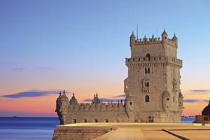 a castle with a clock at the top of Belém Tower