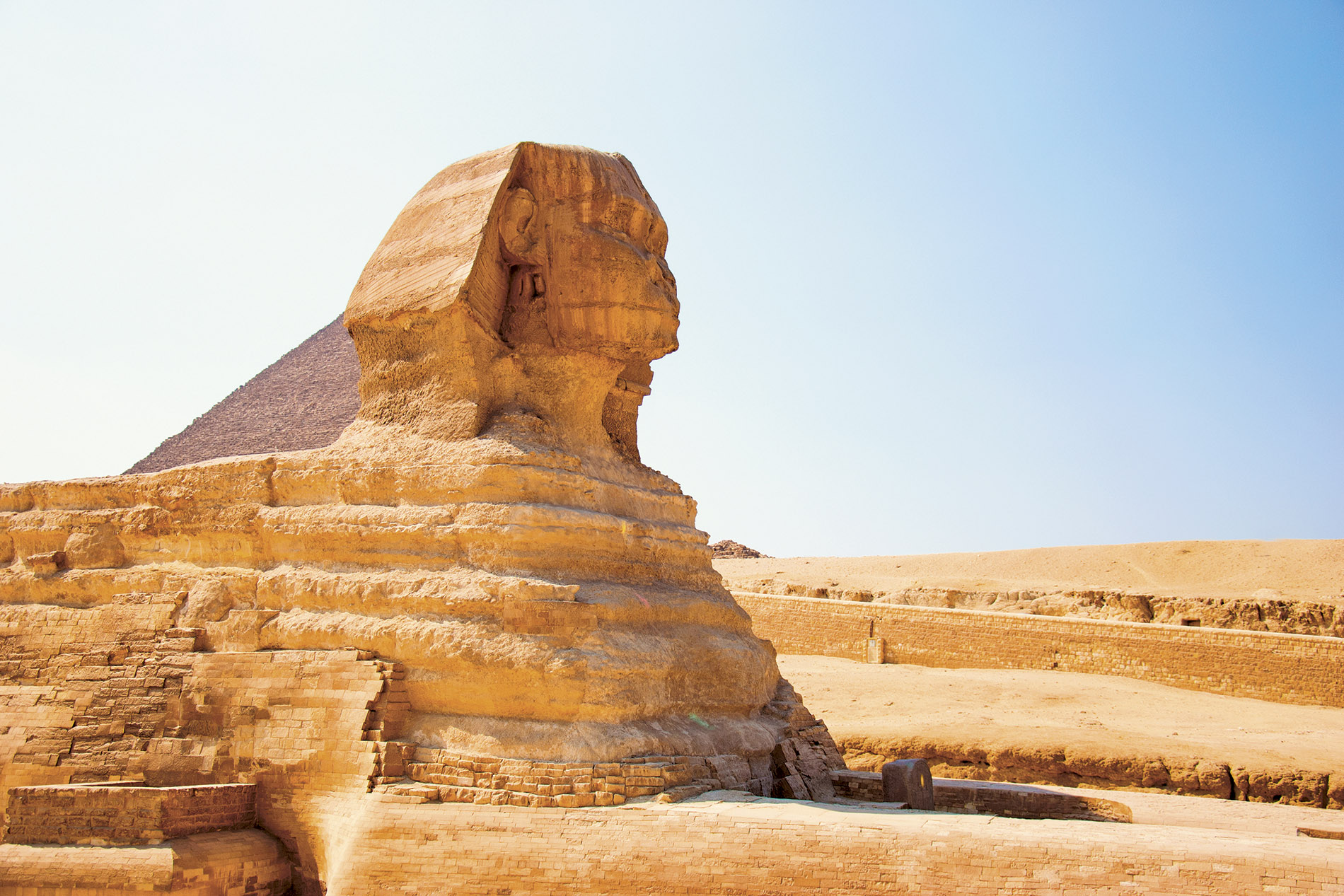 a view of a large rock with Great Sphinx of Giza in the background