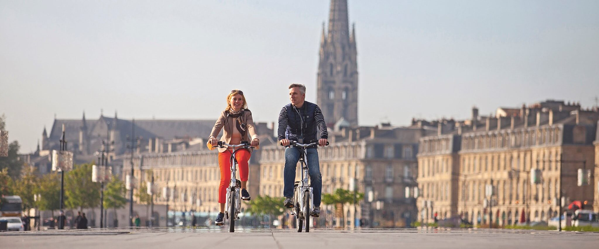 Tourist couple on vacation riding bicycles on the streets of Bordeaux, France
